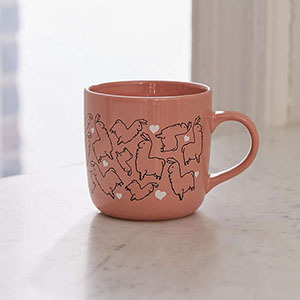Oversized pink ceramic mug with small llama outlines and white hearts printed all over it photo