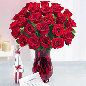 Red roses in a red vase next to a message in a bottle from 1-800 Flowers photo
