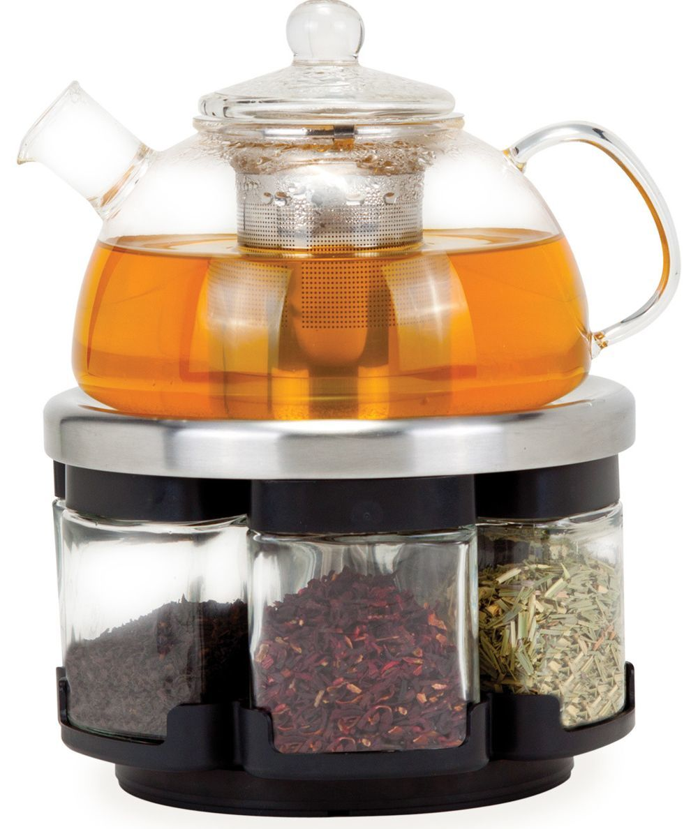 Glass teapot rests on a rack with loose-leaf tea photo