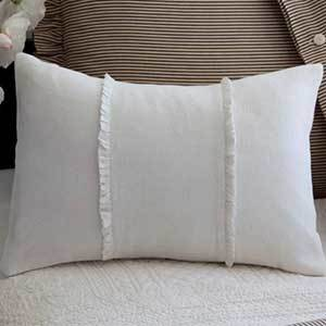 Bright white lumbar pillow with two vertical ruffle stripes equally spaced from the center of the pillow photo