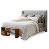 Neutral colored bedset with charcoal gray headboard and wood table at the end of the bed photo