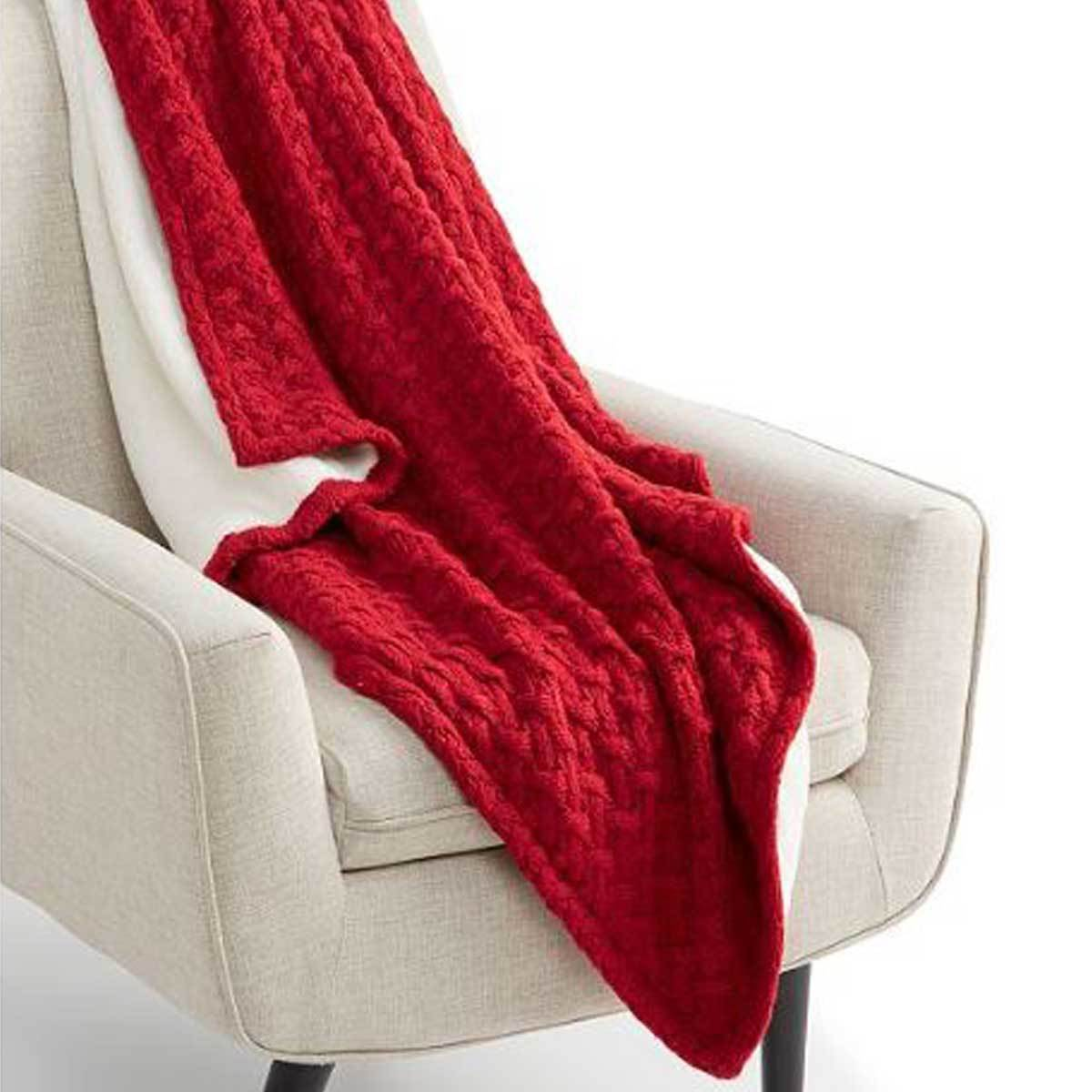 Red sweaterknit throw blanket with white faux fur on a beige armchair photo