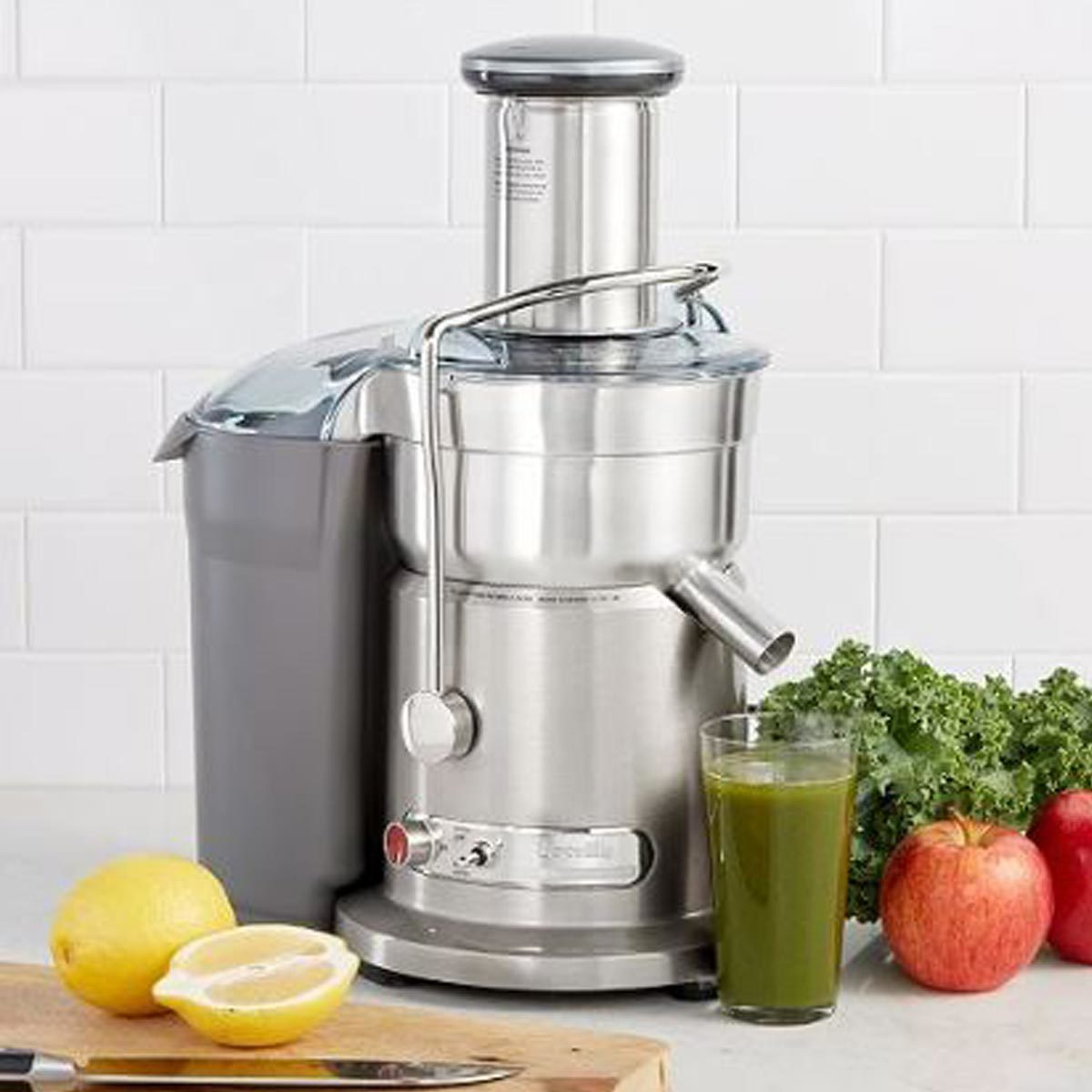 Chrome Breville juicer with cup of green juice and a lemon on a cutting board with knife photo