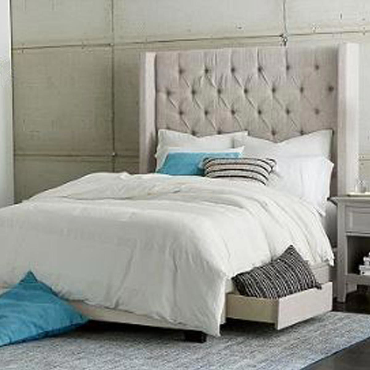 Storage bed with upholstered headboard, white bedding, and blue pillows photo