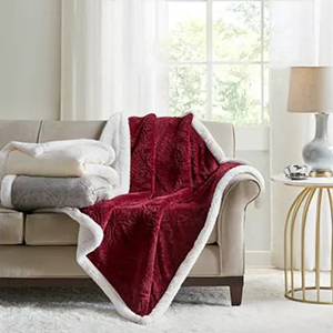 Red throw blanket with white faux fur on a beige couch from Macy's photo