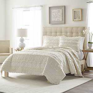 Ivory quilt with a ruffel pattern and matching pillows photo