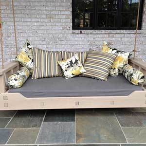 Wood porch swing the size of a bed with a gray cushion and throw pillows photo