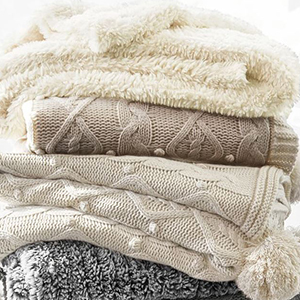 Gray and neutral colored reversible pom pom blankets photo