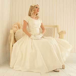 Bride sitting in 50's style vintage wedding dress with gloves photo
