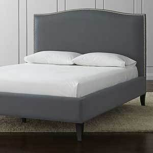 Dark gray upholstered bed with beading around the edges. photo