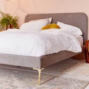 Gray upholstered bed with gold legs. photo