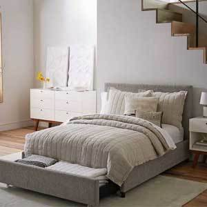 Gray upholstered bed with a pull-out drawer photo