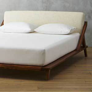 Wooden bed frame with ivory upholstery on the back. photo