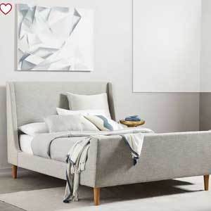 Light gray upholstered bed frame with wooden legs. photo