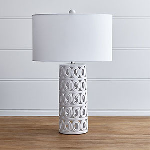 White ceramic table lamp with oval-shaped cutouts. photo