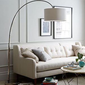 Contemporary overarching floor lamp with a polished nickel base and neutral lampshade. photo