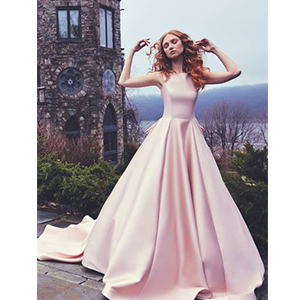 Bride posing in a poofy blush wedding dress with a long train photo