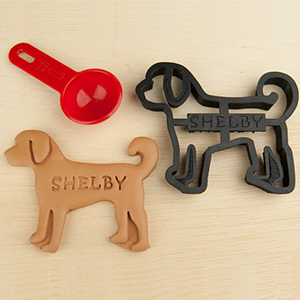 Two customizable Goldendoodle cookie cutters on a table next to a red scoop. photo