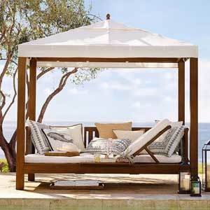 Wood cabana with a white top and white cushions photo