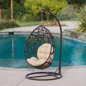 Teardrop chair with a caged design and a white cushion photo