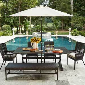 Dining table with matching chairs, a bench, and white umbrella photo