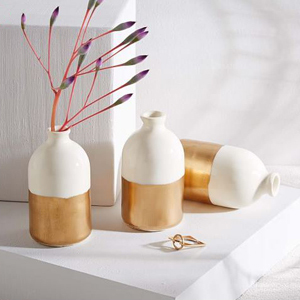 Three vases that are white on top and gold on the bottom with a red plant in one vase from West Elm photo