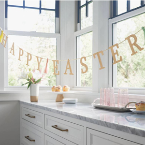 Wooden garland from Target that reads Happy Easter and has tassels in a kitchen with windows and a counter photo