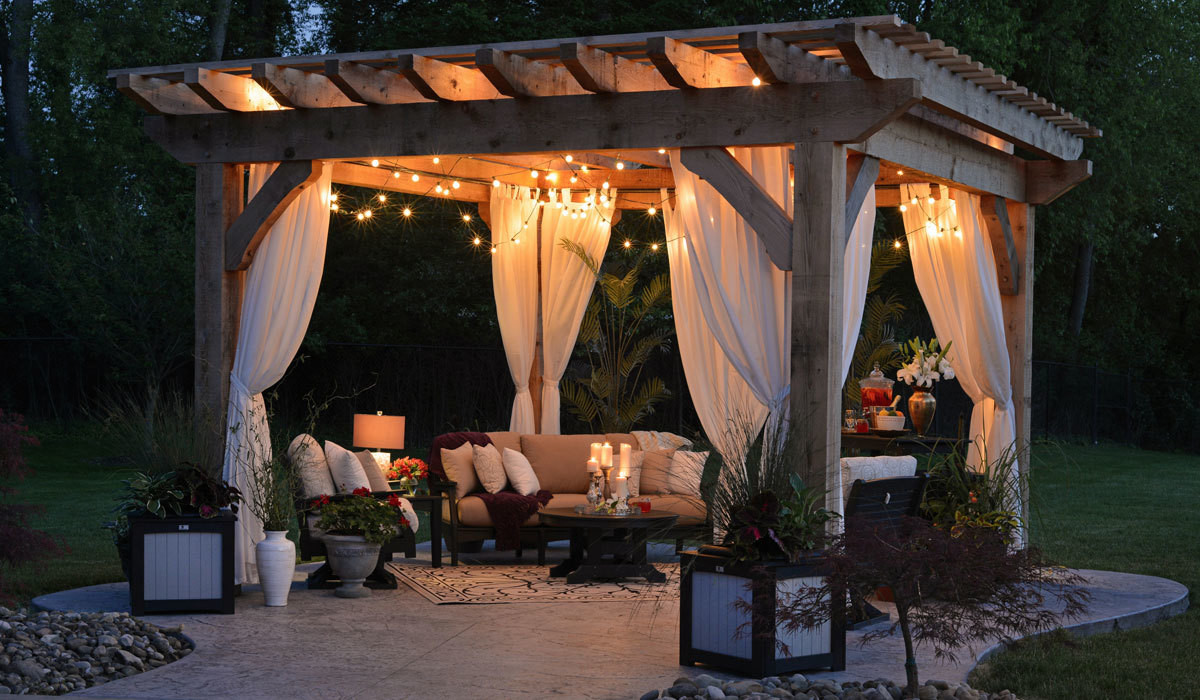 Backyard patio with couches and lights at night
