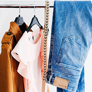 Jacket, pink blouse, belt, and denim jeans hanging in a closet. photo