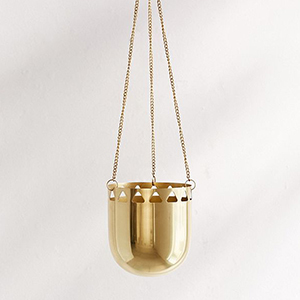 Gold hanging planter with small triangle cutouts. photo