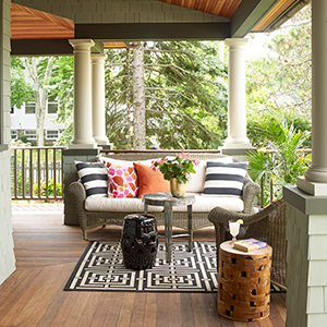 Front porch with wicker couch and chair sitting on it accessorized with black and white striped pillows. photo