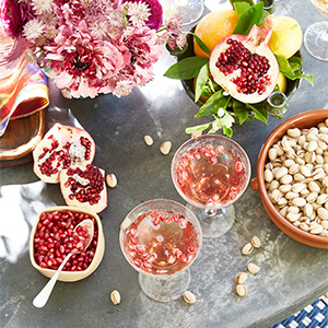 Tabletop view with flowers, glasses full of wine or champagne, a bowl of pistachios, and pomegranates. photo