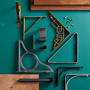 A variety of shelf brackets in differing colors sit atop a teal background. photo