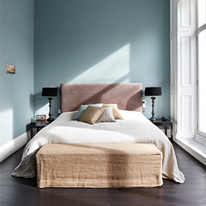 Photo of a bed with a mauve-colored tufted headboard in a light blue bedroom. photo