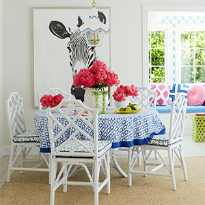 Image of a breakfast nook with a white table covered with a blue printed tablecloth. photo