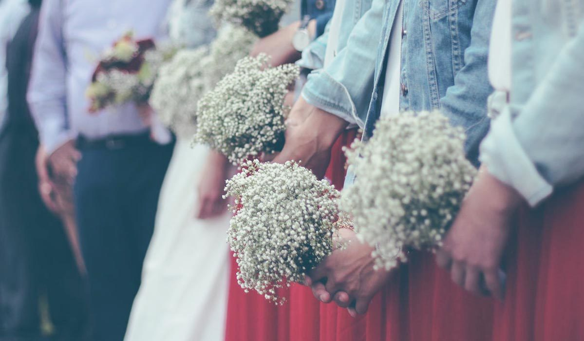 Bridesmaids holding white flowers while wearing jean jackets.