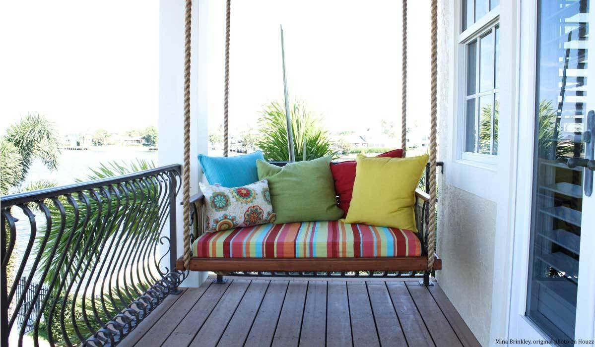 A porch with a porch swing with colorful pillows