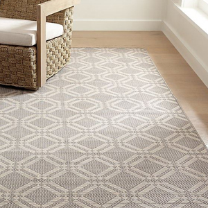grey and white trellis patterned rug with a chair photo