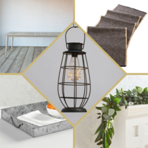 Black caged lantern with light bulb inside paired with garland, a metal tray, a table runner, and a gray table. photo