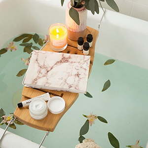 Bamboo bath caddy with a book, candle, lotion, and vase on it photo