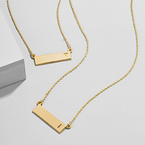 BaubleBar of gold necklaces that has one letter etched on each right side photo