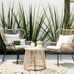 Three piece wicker patio set with white cushions. photo
