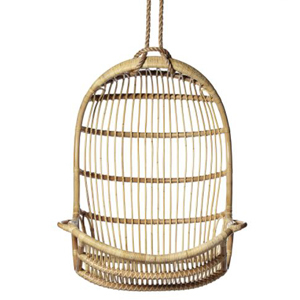 Rattan scoop chair hanging by heavy-duty rope. photo