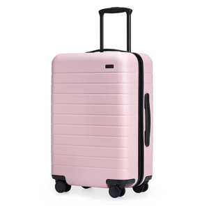 Spinning pastel pink carry-on bag with pull handle at the top. photo