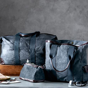 Canvas travel collection featuring a tote, toiletry case, and a weekend bag each featuring leather detailing. photo