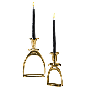 Two gold stirrup candleholders with black candles photo