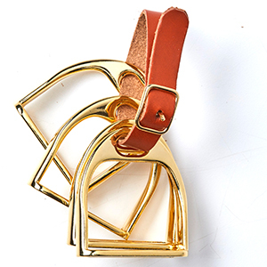 Four napkin rings shaped like stirrups and held together with a leather belt photo