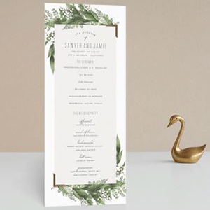 White wedding program with green fern branches framing the top and bottom photo