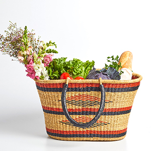 Woven natural basket with red and black stripes and triangles photo