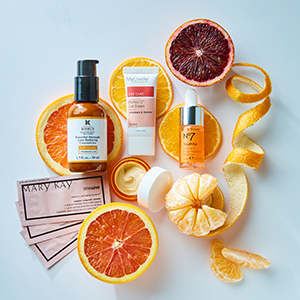 Vitamin C-infused beauty products laying on a light blue background with orange slices on it. photo